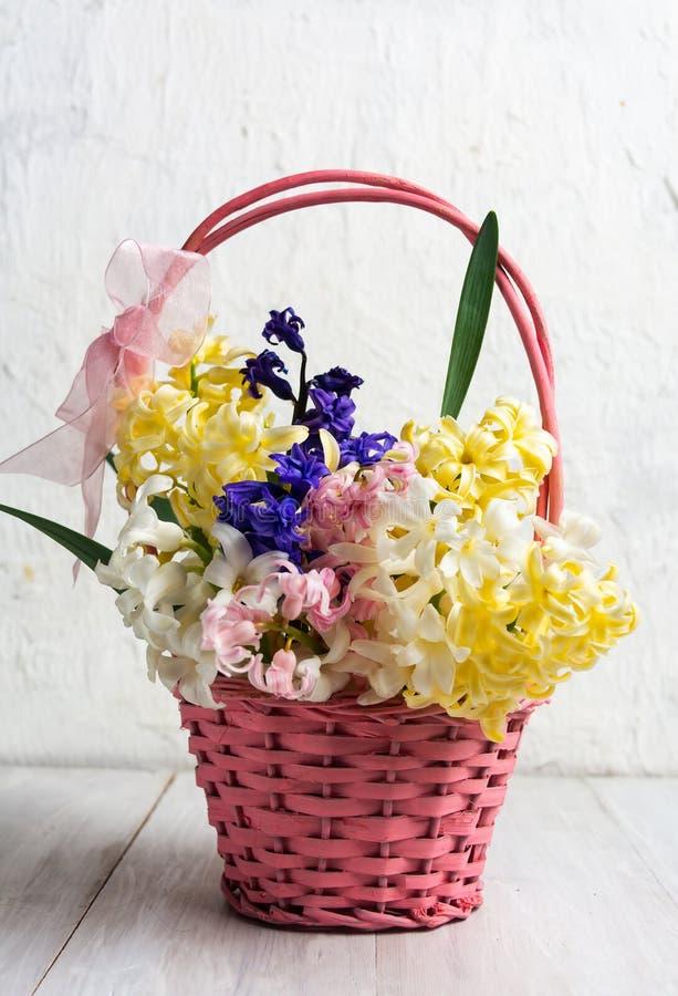Oeufs de pâques et fleurs décorés de ressort dans un panier photos libres de droits