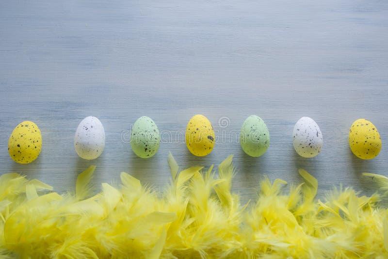 Oeufs de pâques et plumes jaunes sur la table en bois photos libres de droits