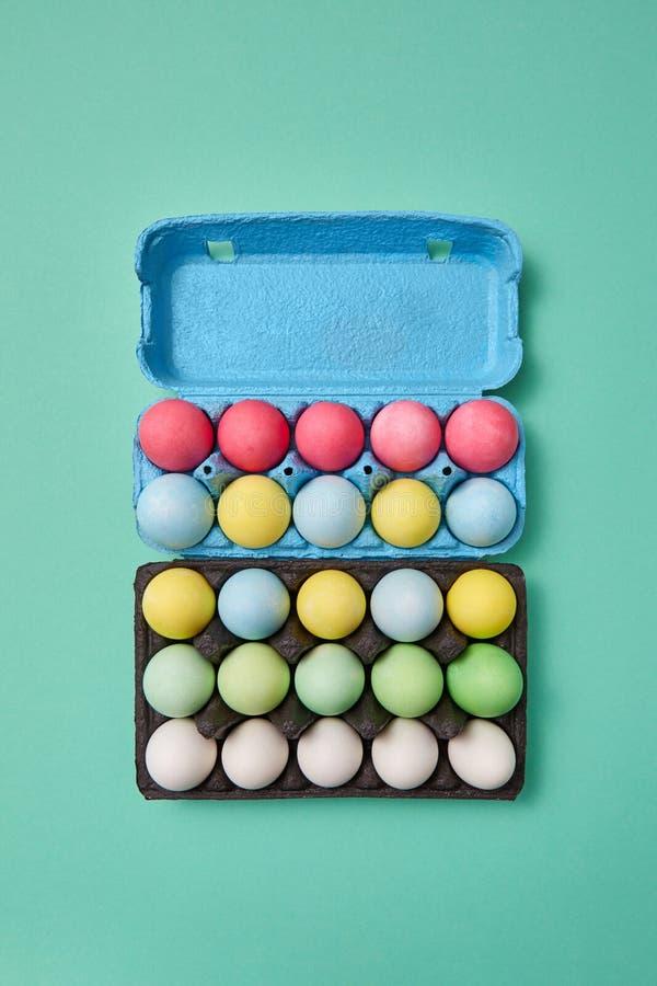 Oeufs de pâques lumineux multicolores dans une boîte en carton bleue et noire sur un fond vert avec l'espace de copie Disposition photos stock