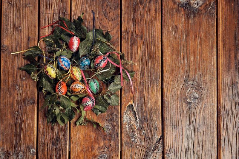 Oeufs de pâques peints à la main décorés des branches vertes de lierre sur un cru, table en bois avec l'espace photo stock