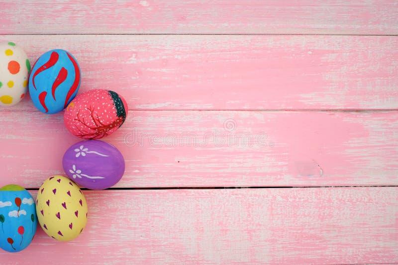 Oeufs de pâques peints à la main en pastel avec le fond rose images stock