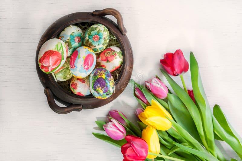 Oeufs de pâques peints dans un pot brun en céramique avec les tulipes colorées sur le fond en bois clair photo stock