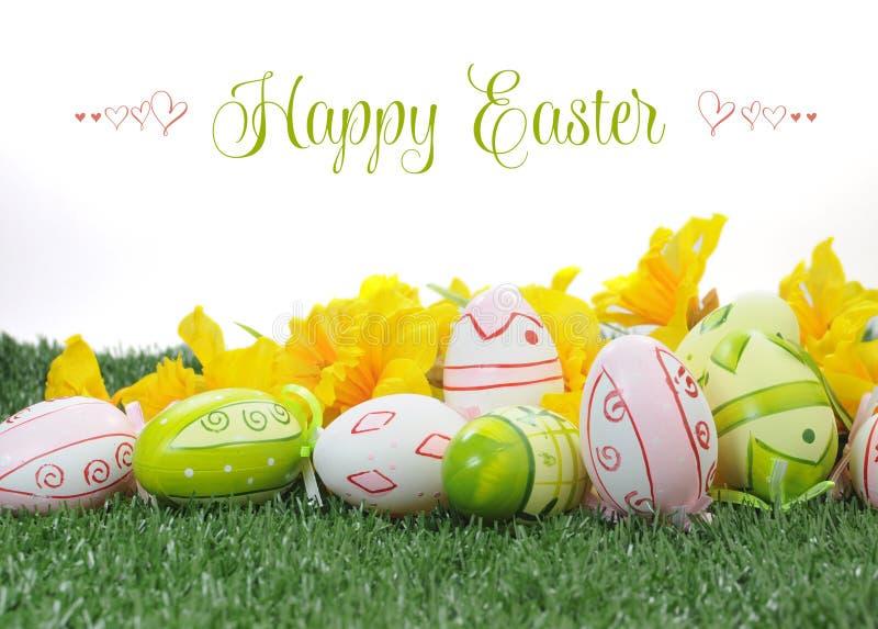 Oeufs de pâques roses de Pâques et verts colorés heureux avec les jonquilles jaunes sur l'herbe verte photos libres de droits