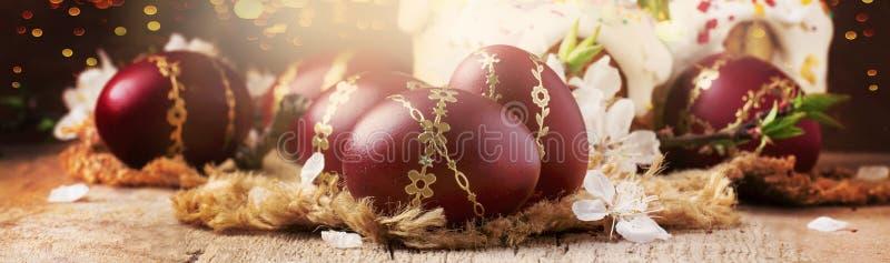 Oeufs de pâques rouge foncé avec le modèle d'or, fleurs d'abricot, fond en bois rustique, bannière de Pâques, foyer sélectif image stock