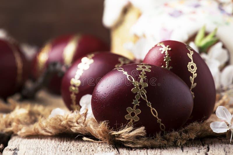 Oeufs de pâques rouge foncé avec le modèle d'or, fleurs d'abricot, fond en bois rustique, foyer sélectif image libre de droits