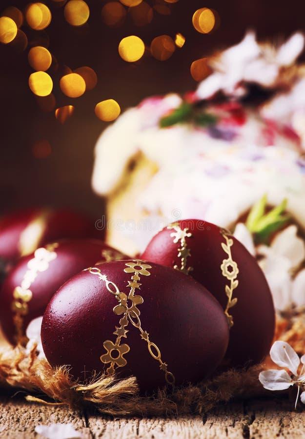 Oeufs de pâques rouge foncé avec le modèle d'or, fleurs d'abricot, fond en bois rustique, foyer sélectif photos stock