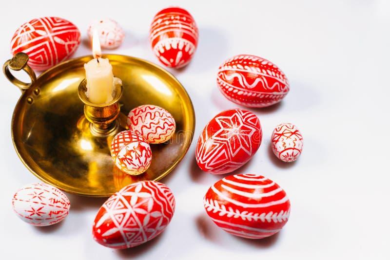 Oeufs de pâques rouges avec le modèle blanc folklorique sur le chandelier avec la bougie brûlante dans le côté gauche sur le fond images stock