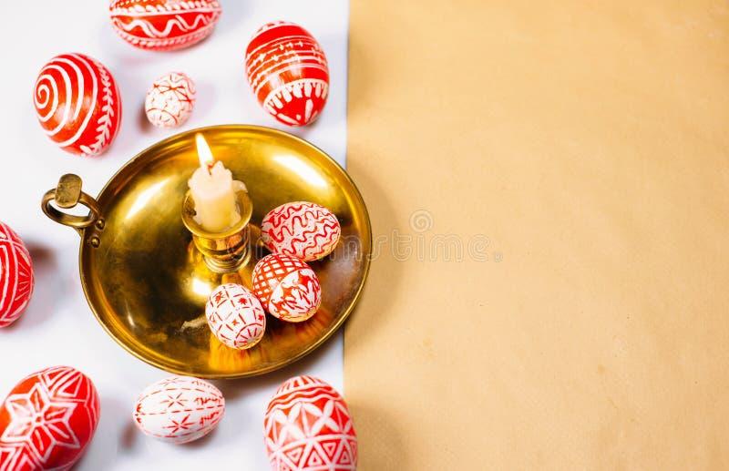 Oeufs de pâques rouges avec le modèle blanc folklorique sur le chandelier avec la bougie brûlante et autour Oeufs traditionnels u photo libre de droits