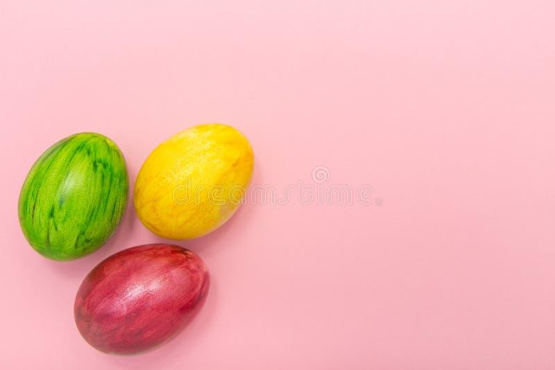 Oeufs de pâques sur le fond rose Style fait main d'oeufs de vert jaune et de rouge foncé le nouveau de la coloration forment la f photo stock