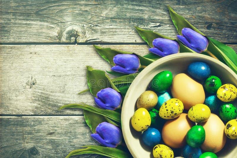 Oeufs de p?ques multicolores dans une cuvette Belles tulipes Copiez l'espace Fond en bois P?ques image stock