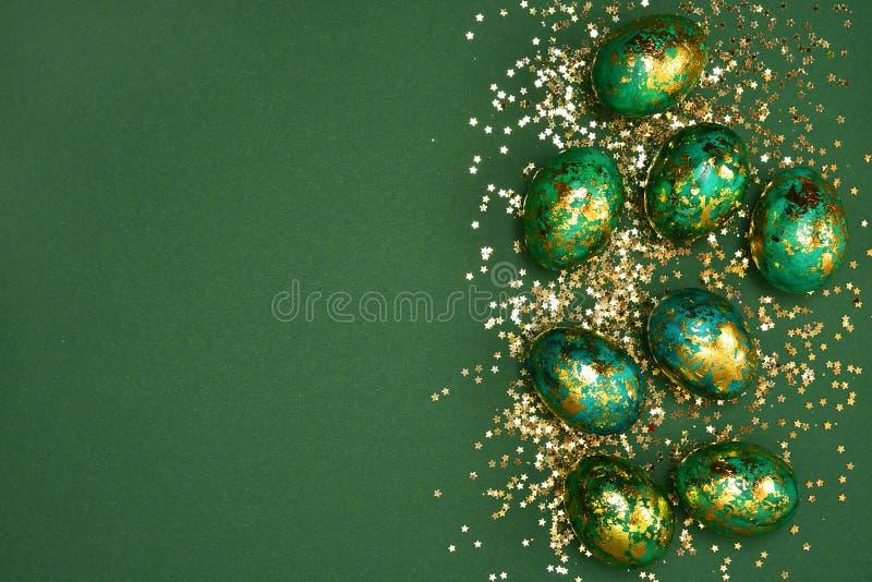 Oeufs de p?ques, vert-fonc? avec de l'or sur un fond vert Vue de ci-avant Configuration plate images libres de droits