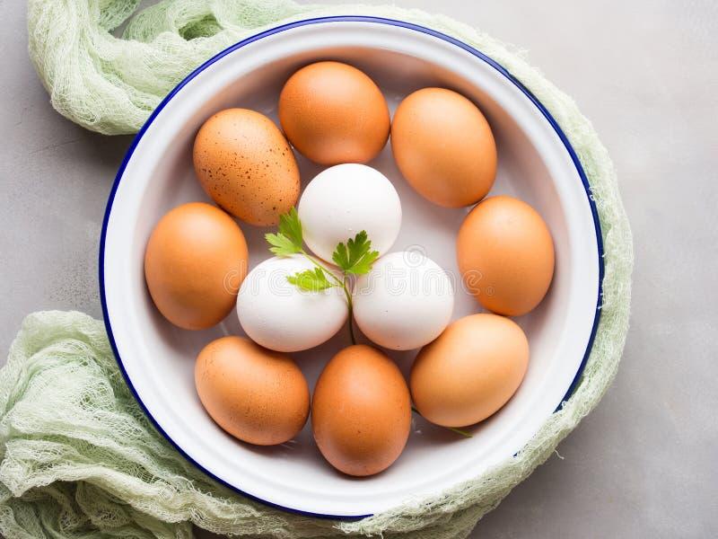 Oeufs de poule blancs et bruns dans la cuvette photos stock