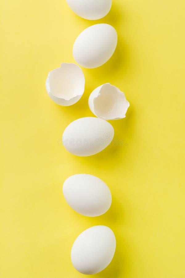OEufs de poulet crus blancs allongés en rang vertical avec oeuf cassé sur fond jaune photographie stock libre de droits