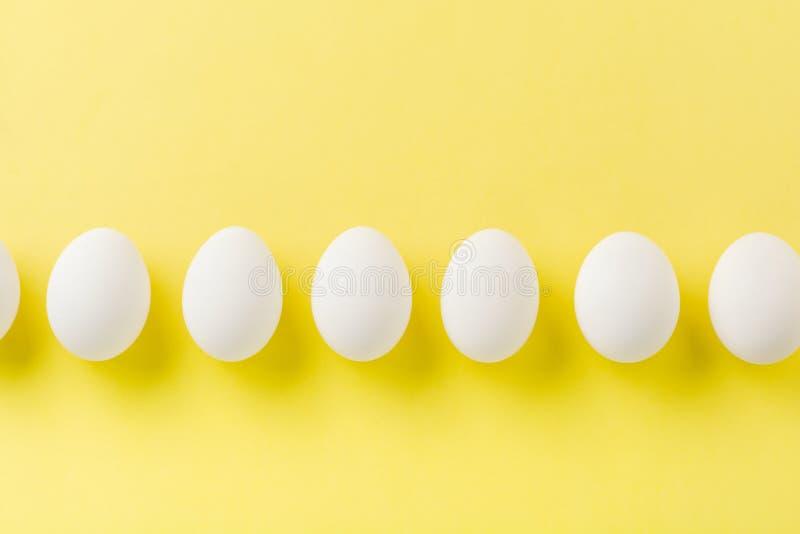 OEufs de poulet crus blancs allongés sur une rangée horizontale avec oeuf cassé sur fond jaune images stock