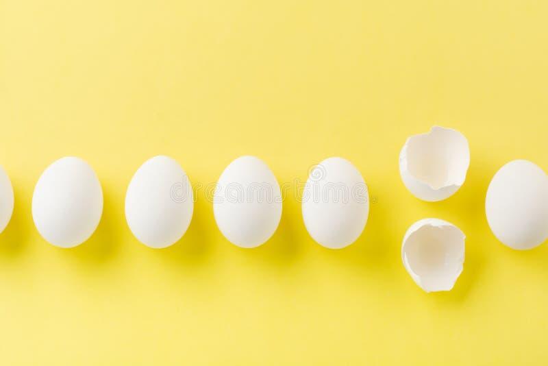 OEufs de poulet crus blancs allongés sur une rangée horizontale avec oeuf cassé sur fond jaune image libre de droits