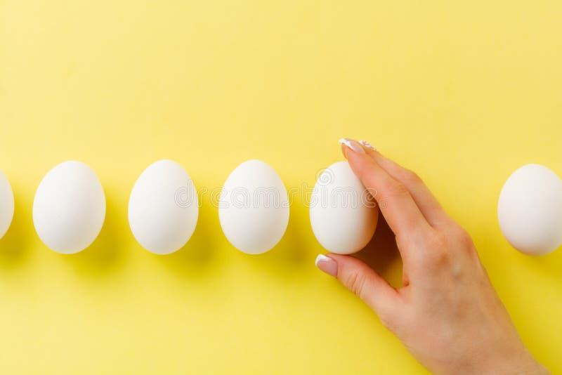 OEufs de poulet crus blancs sur fond jaune clair et la main de la femelle tient un oeuf cassé images stock