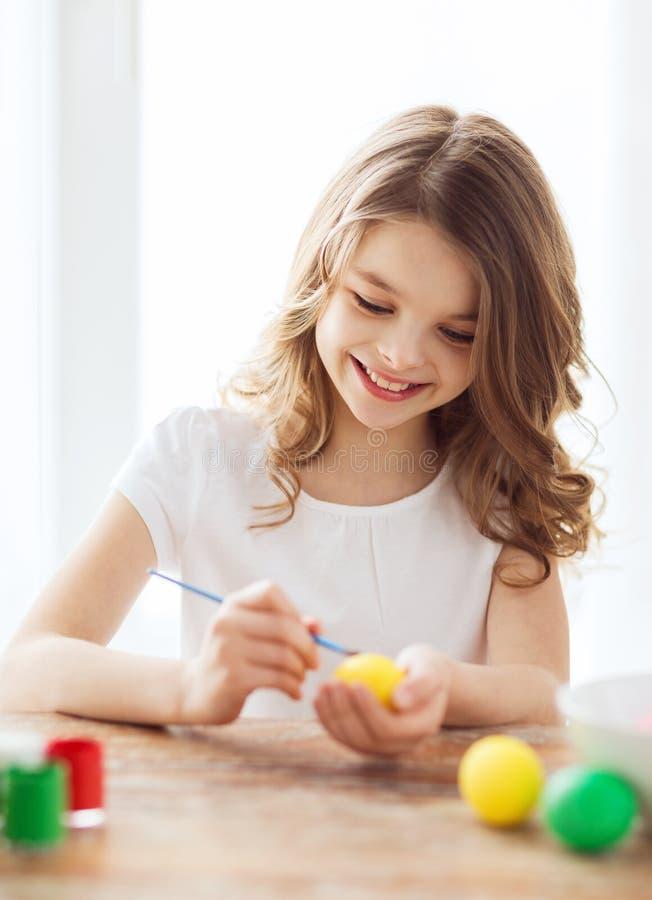 Oeufs de sourire de coloration de petite fille pour Pâques image stock