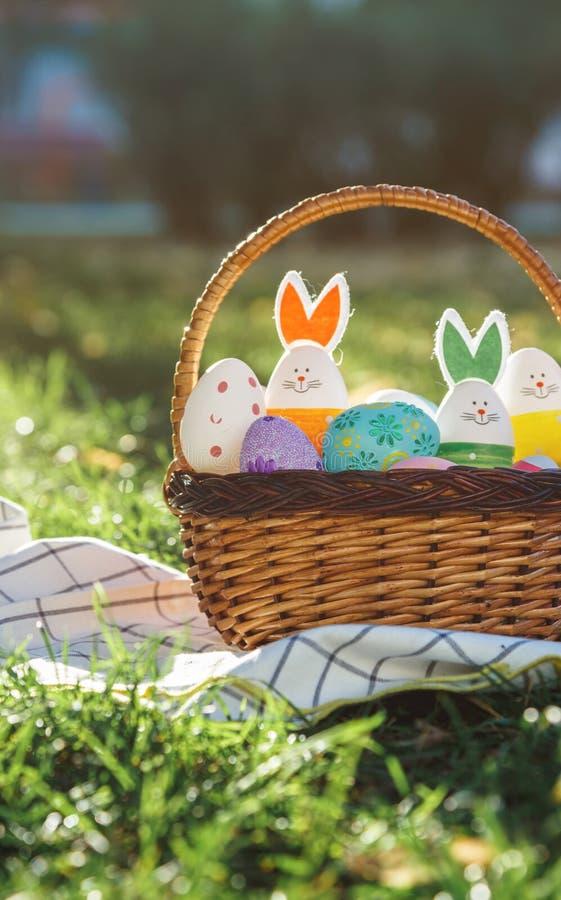 Oeufs et lapin de pâques peints à la main dans le grand panier de rotin sur l'herbe verte sur la serviette blanche Décoration tra photographie stock