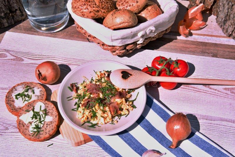 Oeufs faits maison frais de petit déjeuner, oignon et jambon frit, ensemble sur une table en bois image stock