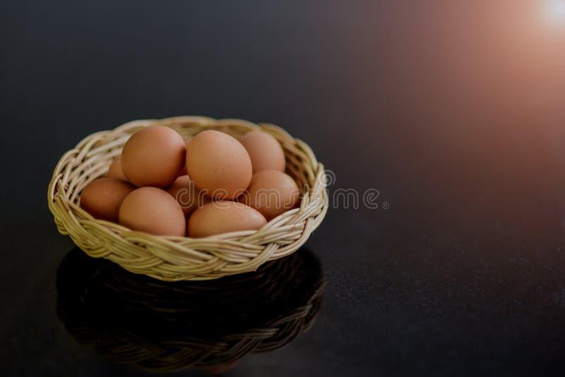 Oeufs frais dans beaucoup de paniers en osier sur une table en pierre noire préparée comme matière première pour la cuisson image libre de droits