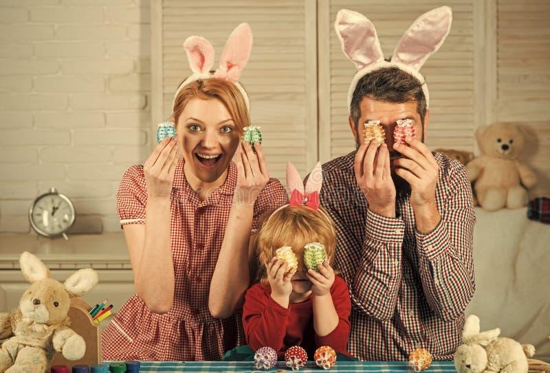 Oeufs heureux de peinture de famille de Pâques photos stock
