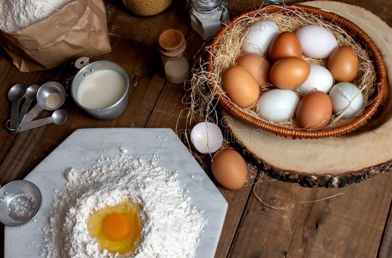 Oeufs, pâte et farine sur la table en bois avec le fond de floc pour un objet dans une boulangerie photographie stock libre de droits
