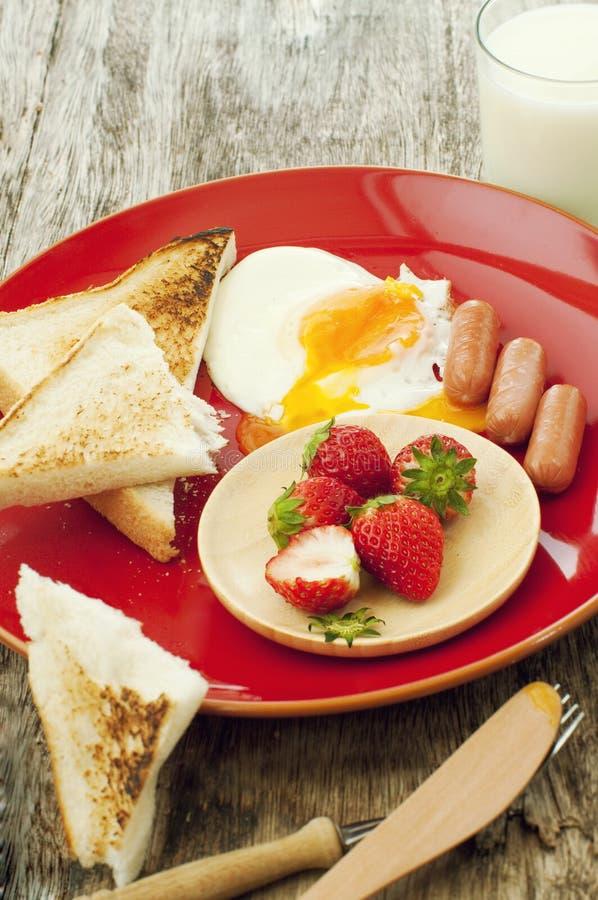 Oeufs, pain grillé, saucisses et fraises photo libre de droits