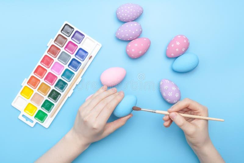 Oeufs peints à la main de Pâques de vacances avec le poulet sur la table photographie stock libre de droits