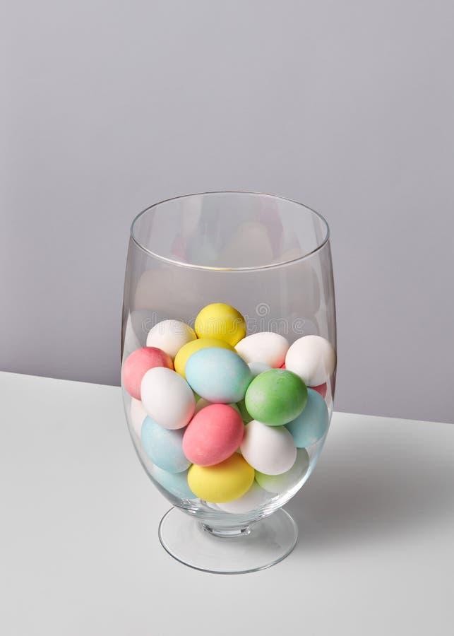 Oeufs peints multicolores dans un vase en verre sur un fond gris avec l'espace pour le texte Concept de Pâques images stock