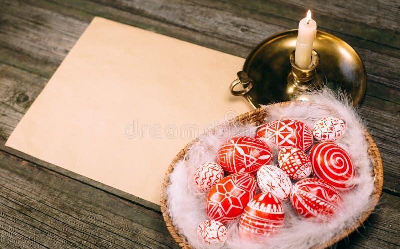 Oeufs rouges de Pâques avec le modèle blanc folklorique dans le panier, près du chandelier sur le conseil en bois rustique Oeufs  image libre de droits