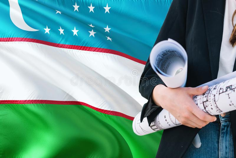 Oezbekistaanse de holdingsblauwdruk van de Architectenvrouw tegen golvende de vlagachtergrond van Oezbekistan Bouw en architectuu royalty-vrije stock afbeelding