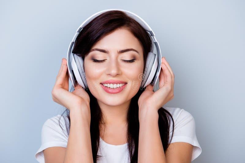 Oförsiktig le kvinna i hörlurar som lyssnar till hennes gunstling arkivbild