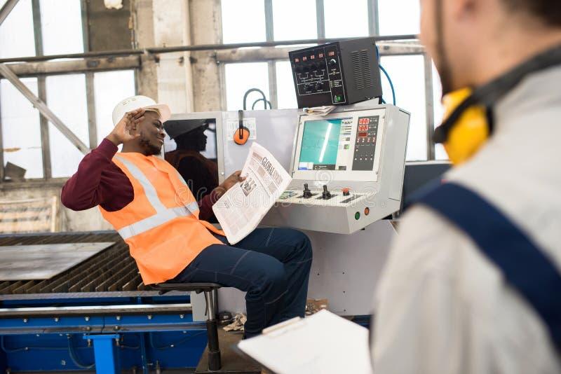 Oförsiktiga fabriks- anställda som pratar på arbetsplatsen royaltyfria foton
