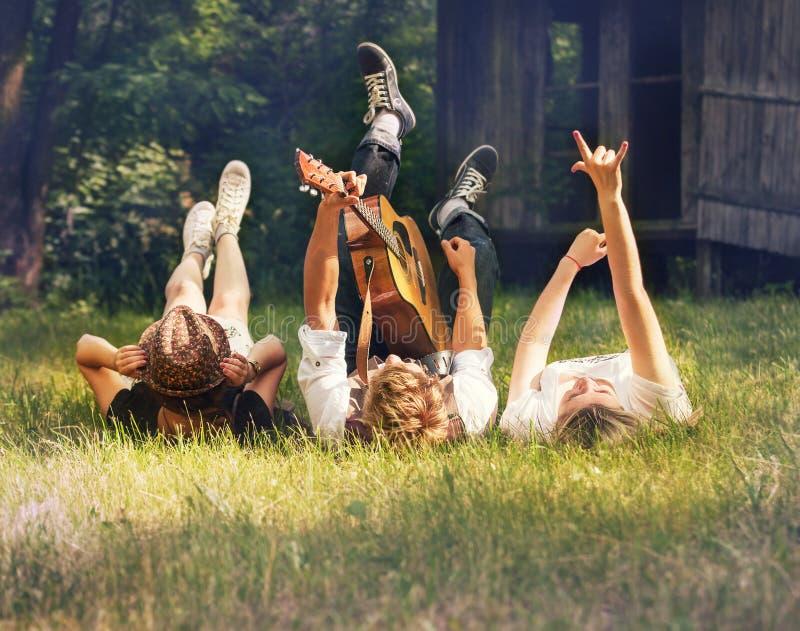 Oförsiktiga tonåringar som ligger på den gröna gräsmattan med gitarren arkivfoto