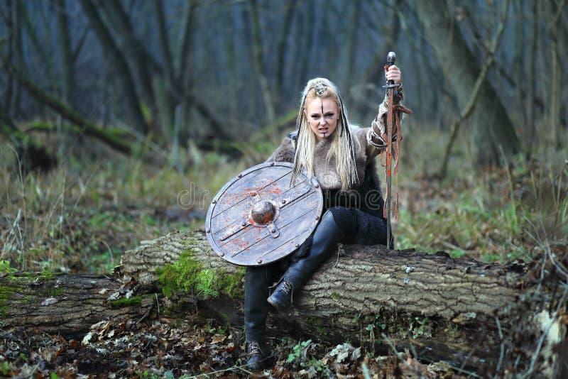 Oförskräckt blond nordlig krigarekvinna i skog med skölden och svärdet i den nedblodade handen arkivbild