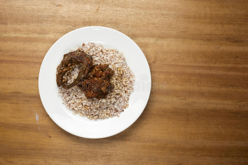 Ofada rice served with chunks of meat spiced in a pepper sauce and kpanla fish. A serving of a staple african delicacy royalty free stock photo