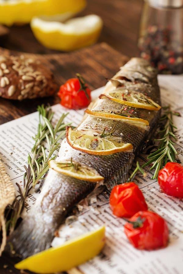 Ofen-gebackener Wolfsbarsch mit Zitrone und Kräutern Seebarschfische, völlig gebacken lizenzfreie stockfotos