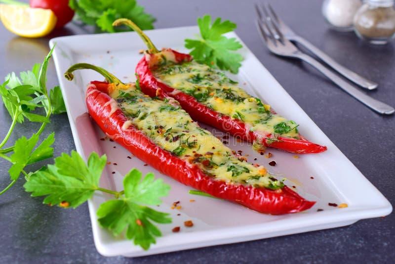 Ofen gekochter roter Paprika angefüllt mit Käse, Knoblauch und Kräutern auf einer weißen Platte mit parcley und Kirschtomaten lizenzfreie stockfotografie
