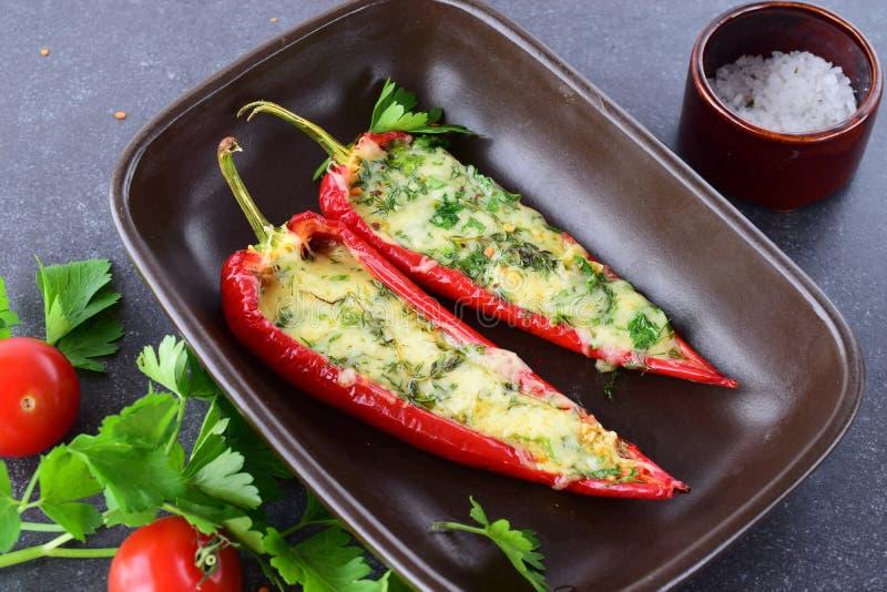 Ofen gekochter roter Paprika angefüllt mit Käse, Knoblauch und Kräutern in einer keramischen Form auf einem abstrakten grauen Hin stockfotos