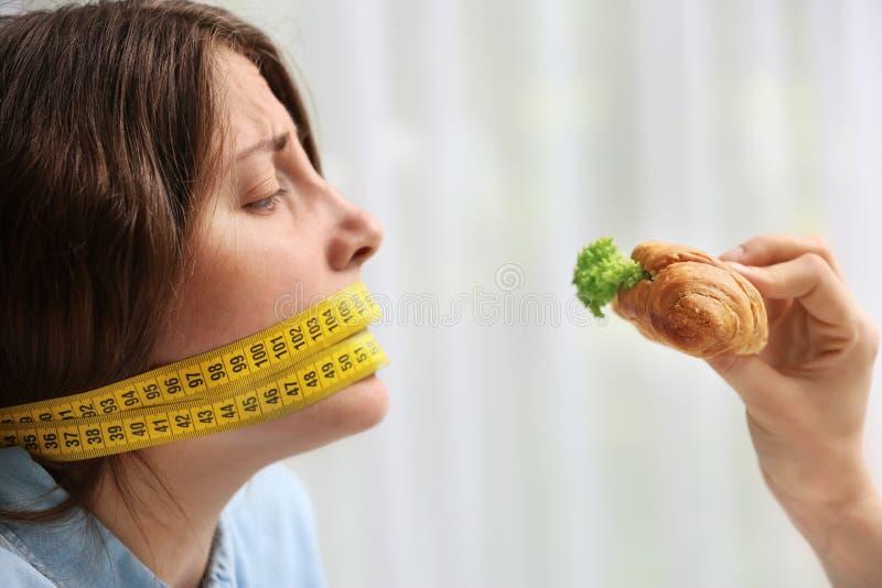 Oferecimento do sanduíche saboroso do croissant à jovem mulher com a fita de medição em torno de sua boca no fundo claro Fa?a die fotografia de stock royalty free