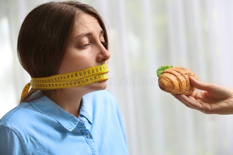 Oferecimento do sanduíche saboroso do croissant à jovem mulher com a fita de medição em torno de sua boca no fundo claro Fa?a die imagem de stock