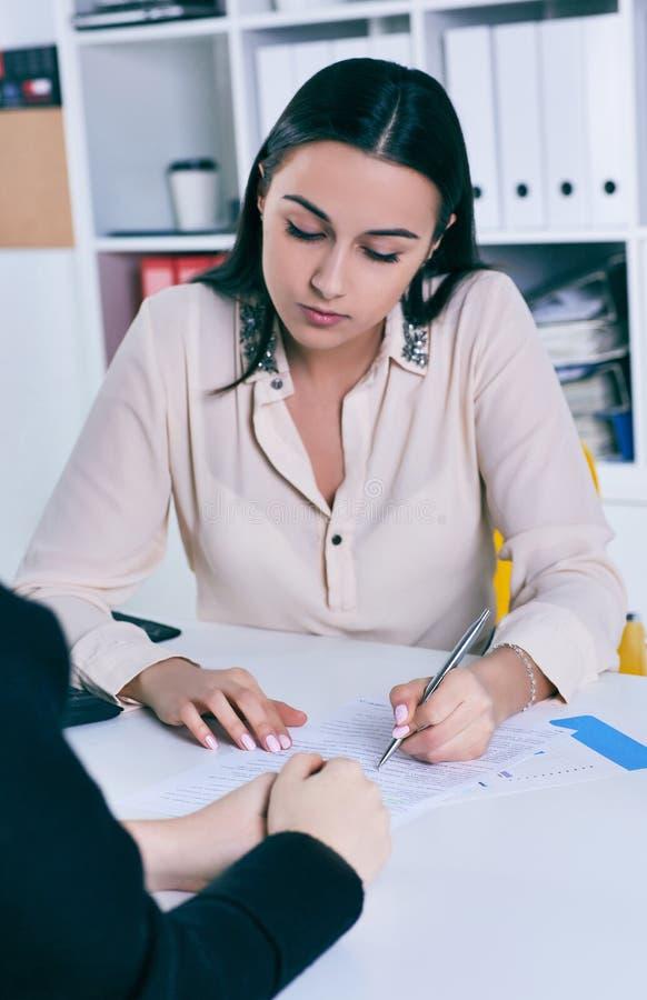 Oferecimento europeu da mulher, ensinando uma mulher asiática pobre falar a língua inglesa foto de stock