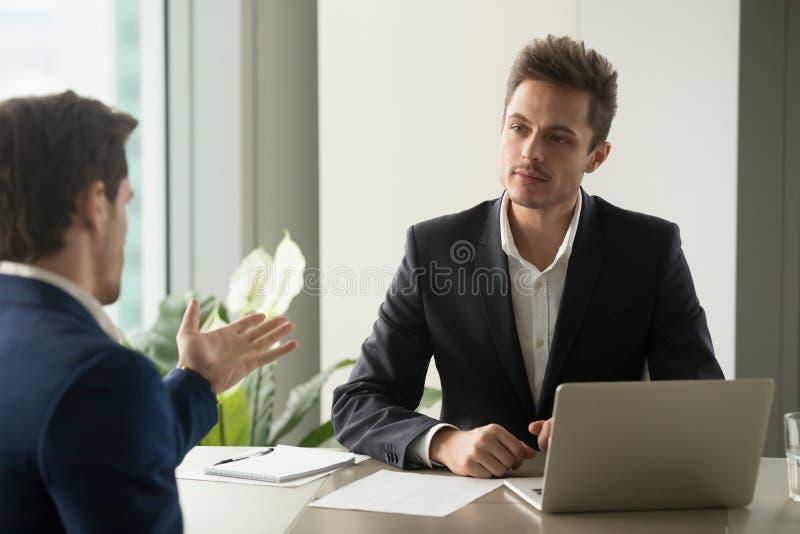 Oferta de escuta focalizada dos sócios do homem de negócios boa imagens de stock royalty free