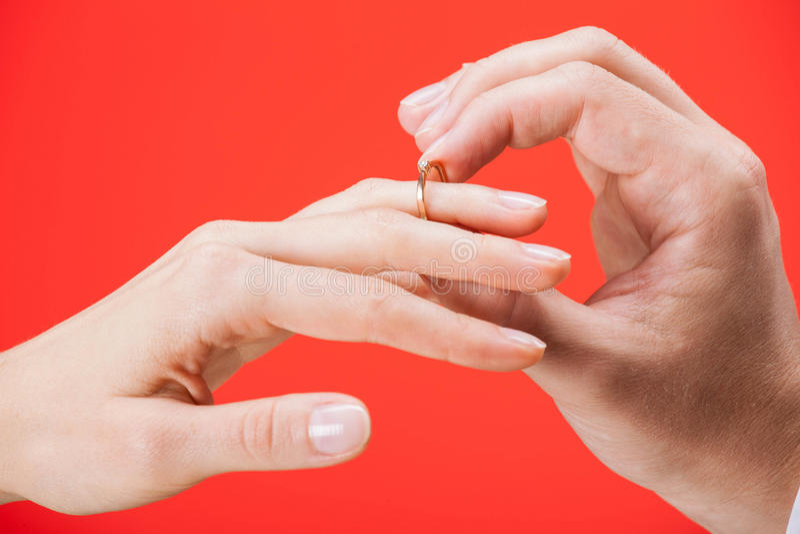 Oferta de la boda: hombre que pone el anillo de compromiso en un finger de foto de archivo