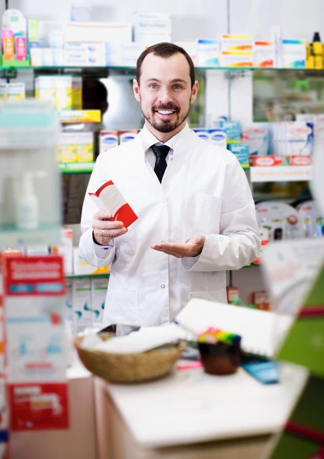 Oferta de sorriso da medicina do homem que mostra a droga direita imagens de stock royalty free