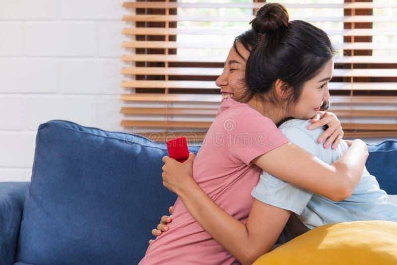 Oferta lesbiana de los pares asiáticos felices con el anillo para casarse en la sala de estar en casa Concepto de la forma de vid imagen de archivo libre de regalías