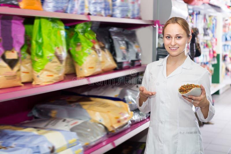 Ofertas adultas del ayudante de tienda para elegir el alimento para animales fotografía de archivo libre de regalías