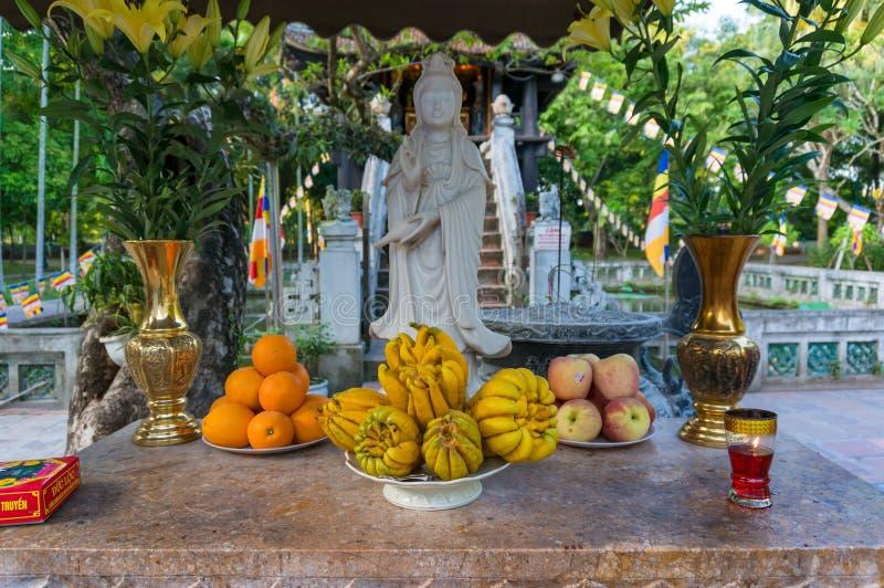 Ofertas de frutos tropicais frescos à estátua da Buda fotos de stock