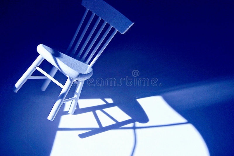 Off Balance. Chair tilts over stock photography