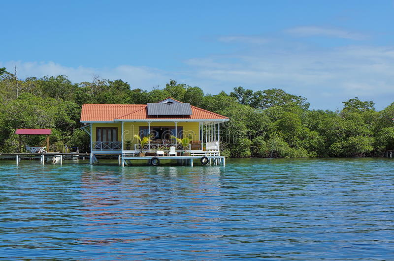 Off-grid house over the sea with solar panels stock photography